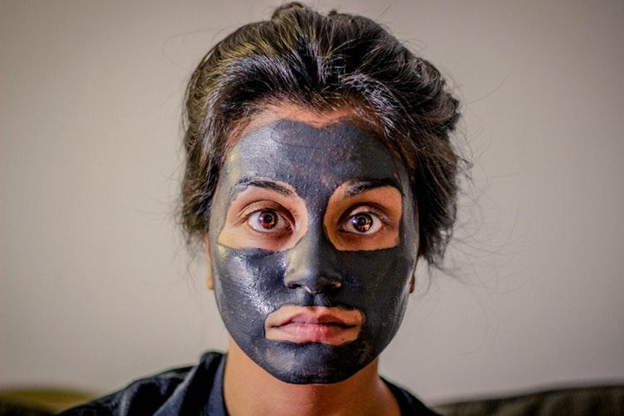 woman wears a charcoal face mask